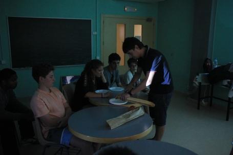 Guest speaker Jordi Miquela prepares pa amb tomàquet (bread with tomato) for students